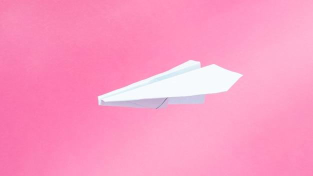 Синий самолет оригами на розовом фоне, путешествия полеты копируют пространство.