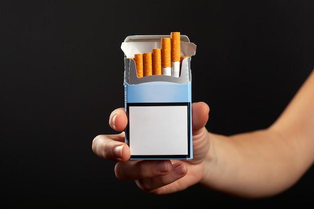 手にタバコの青いパック