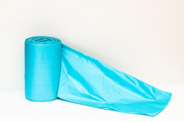 白い背景の上の青い包装ゴミ袋。