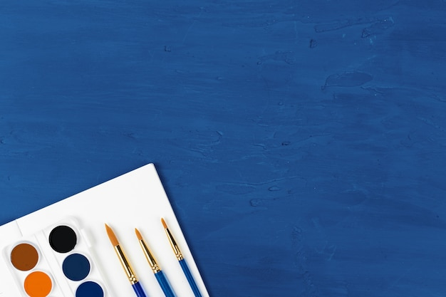 Blue paint brushes on classic blue background, view from above