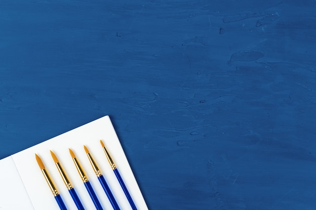 Blue paint brushes on classic blue table, view from above
