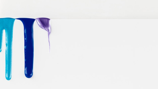 Blue paint dripping on white background
