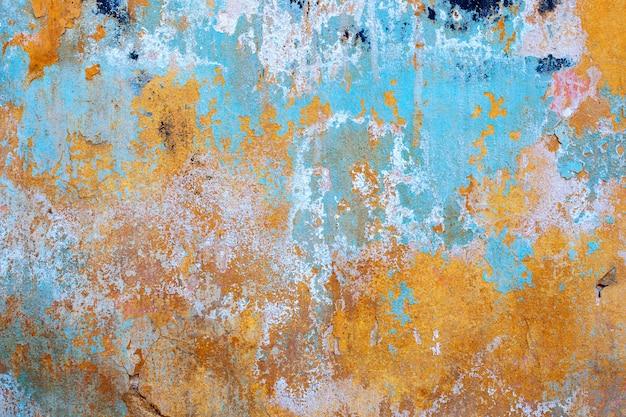 黄色の壁に青いペンキ。抽象的な背景。古い壁のテクスチャ。漆喰の粗面。