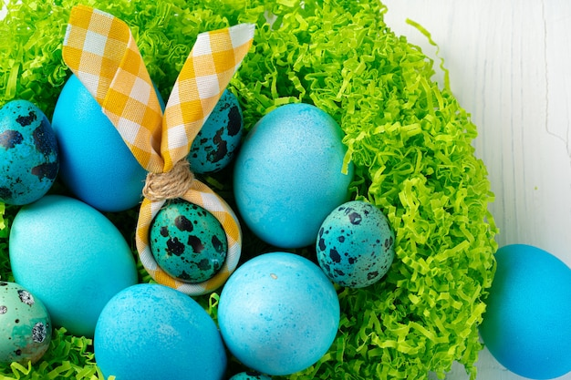 Blue painted eggs in a nest for easter