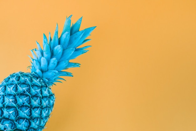 Blue painted pineapple against yellow backdrop