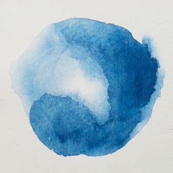 Blue paints in form of round on white paper