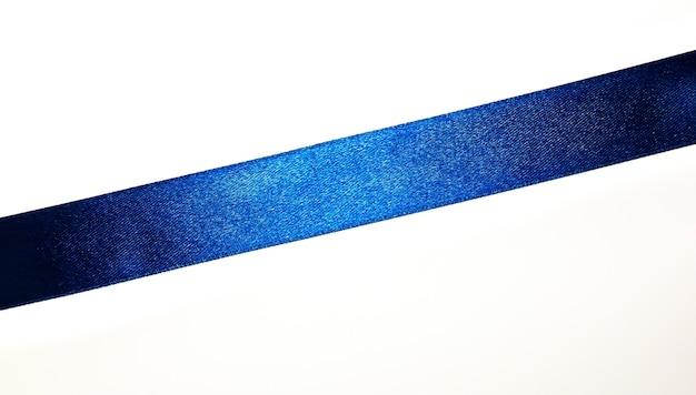 白い背景の上の青いパントンリボン。スタイリッシュな休日の装飾、新年の色のトレンド。