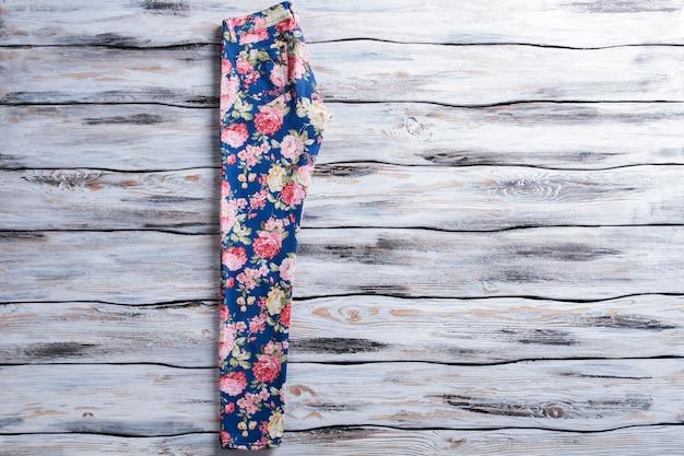플라워 패턴의 블루 팬츠. 나무 바탕에 꽃 바지입니다. 세련된 프린트의 여성용 팬츠. 인기 의류 판매.