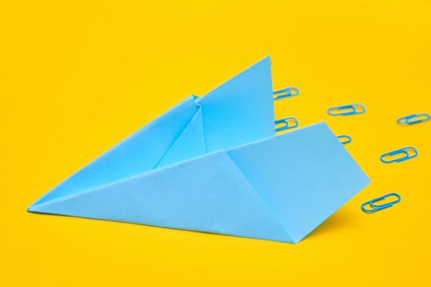 Синий бумажный самолетик на желтом фоне