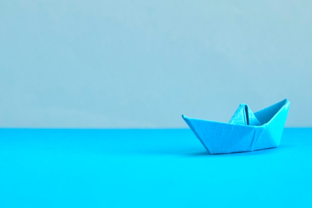 Blue paper boat on cyan background.  concept for leadership, management, business, motivat