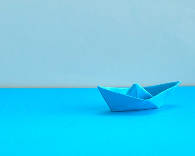 Blue paper boat on cyan background.