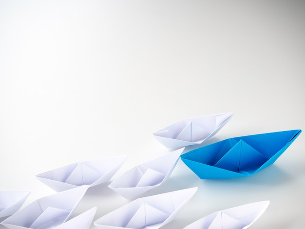 Blue paper boat leading among white ships