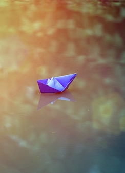 Blue paper boat in a puddle after the rain, summer