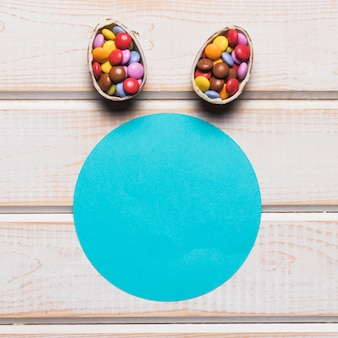 Blue paper circular frame with easter eggs filled with colorful gem candies over the wooden desk