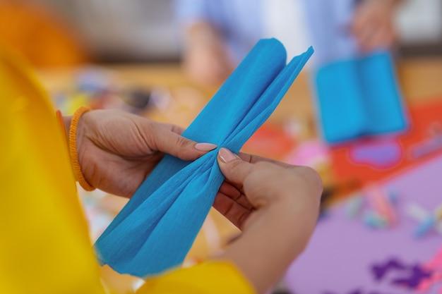 青い紙。適用された装飾のための青い紙を保持しているベージュのネイルアートで先生のクローズアップ