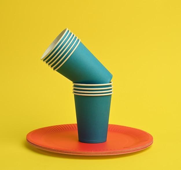青い紙コップ、黄色の背景に赤いプレート。プラスチック拒否の概念、ゼロウェイスト