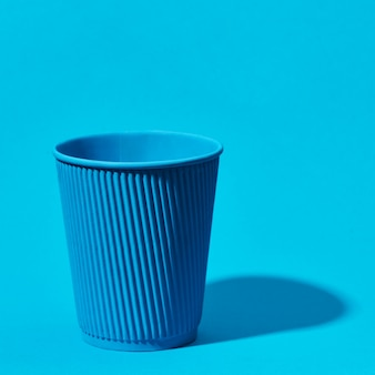 Blue paper cup standing on solid blue