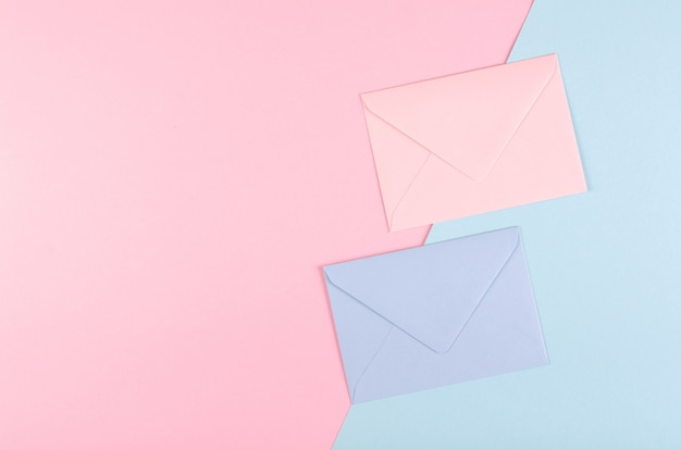 Blue paper envelope composition on pink background.