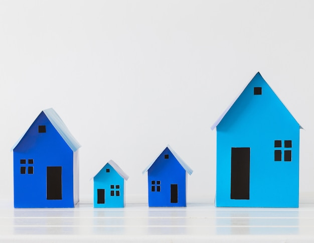 Blue paper houses on white space