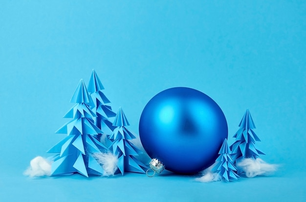 Blue paper origami christmas trees with silver ball decoration