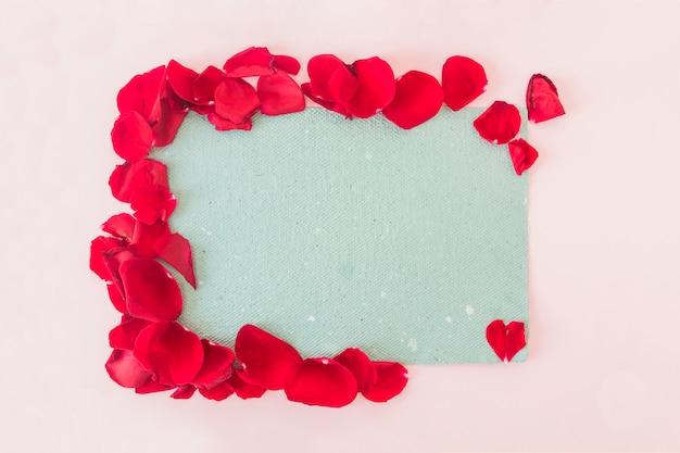 Carta blu e petali di fiori rossi