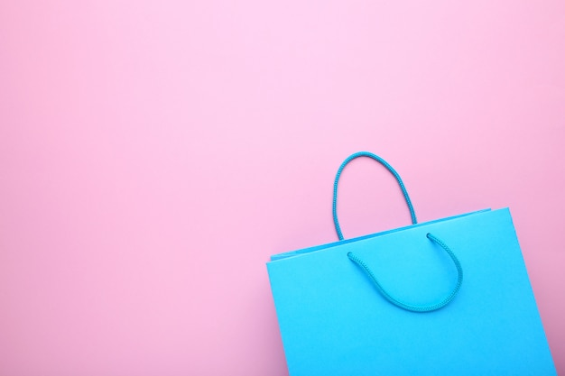 Blue paper shopping bag on pink background