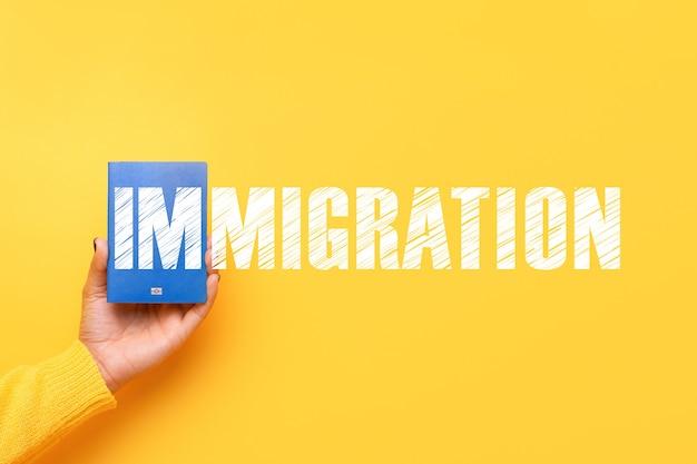 黄色の背景、移民の概念の手に青いパスポート