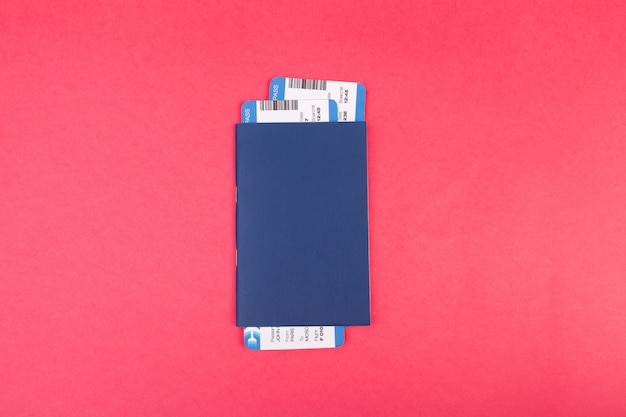 Blue passport with two flight tickets in it on pink  top view