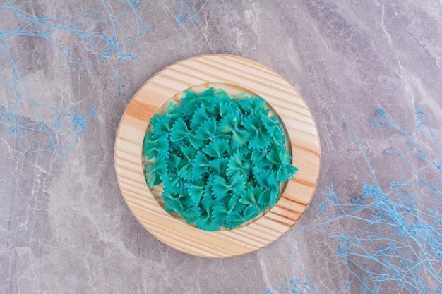 大理石の木製プレートの青いパスタ