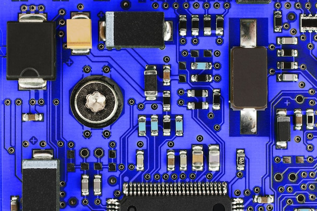 Синяя печатная плата с электронными и электрическими компонентами