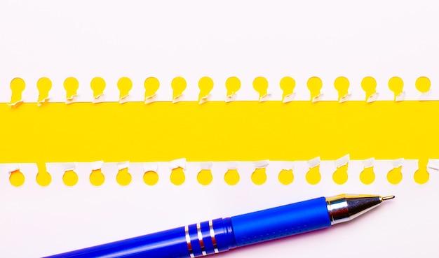 テキストやイラストのコピースペースと明るい黄色の背景に青いペンと白い破れた紙のストリップ。レンプレート