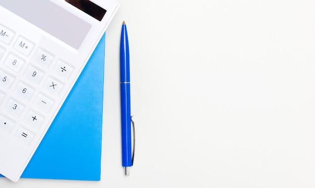 コピースペースのある明るい背景に青いペン、白い電卓、青いメモ帳。ビジネスコンセプト