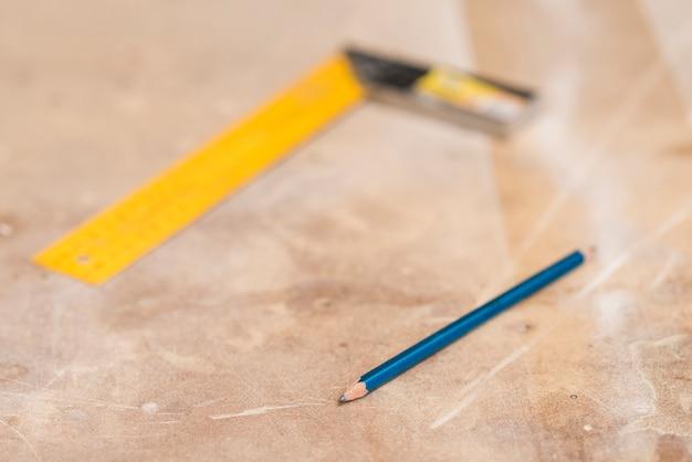 木製の表面に青い鉛筆とぼやけた定規