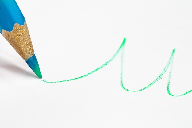 Blue pencil draws a wavy line in green