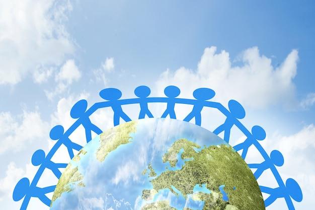 Бумага синих людей, взявшись за руки, стоя на земле. концепция всемирного дня народонаселения