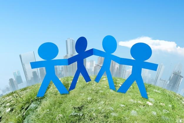 Бумага синих людей, взявшись за руки, стоя на городе. концепция всемирного дня народонаселения