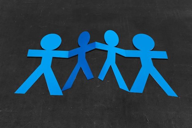 Бумага синих людей, взявшись за руки с черным фоном. концепция всемирного дня народонаселения