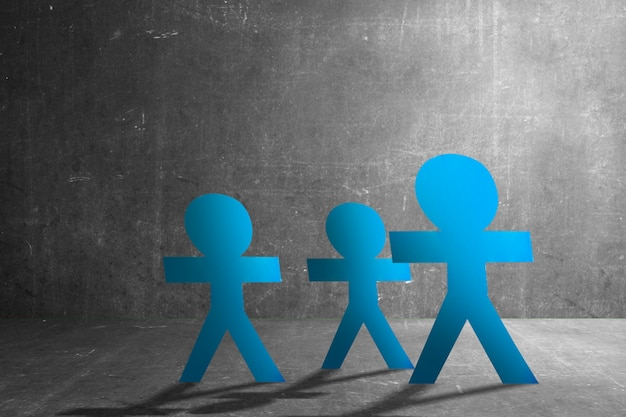 Бумага синих людей, стоящая на фоне черной стены. концепция всемирного дня народонаселения