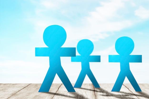 Бумага синих людей, стоящая на фоне голубого неба. концепция всемирного дня народонаселения