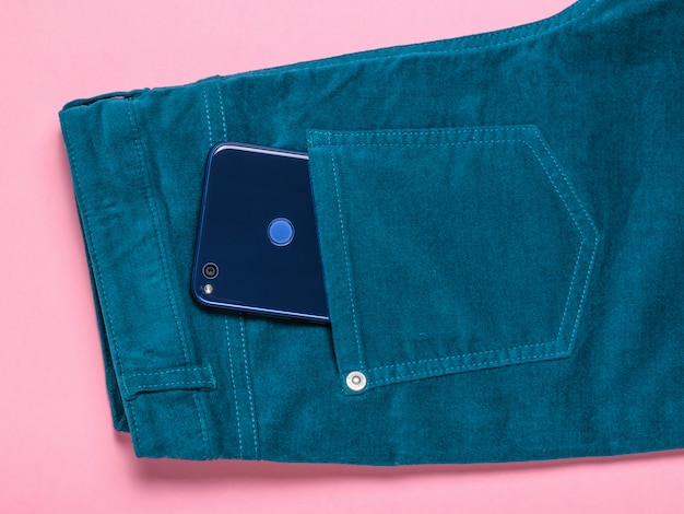 Blue phone sticking out of the pocket of green jeans on pink table. the concept of modern fashion for electronic devices.