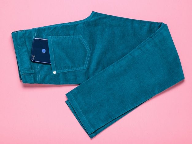 A blue phone sticks out of a pocket of green jeans on a pink.