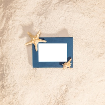 Blue photo frame with dried star on beach