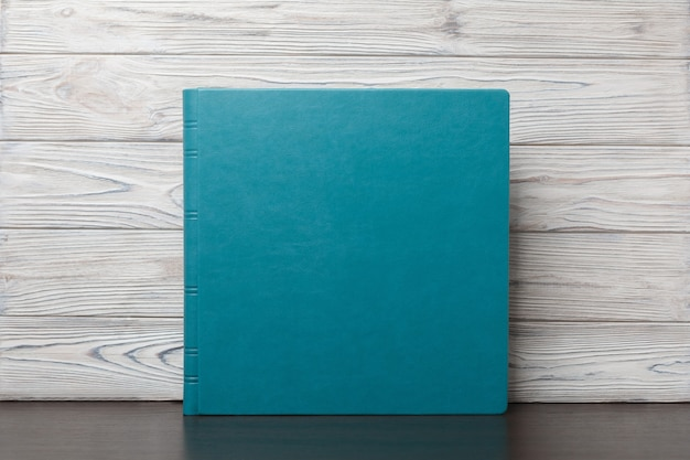 Blue photobook on a wooden table