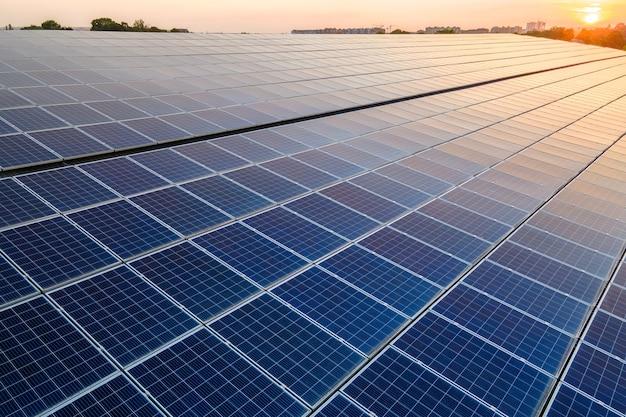 일몰 시 깨끗한 생태 전기를 생산하기 위해 건물 지붕에 파란색 태양광 패널을 장착했습니다. 재생 에너지 개념의 생산입니다.