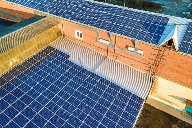 クリーンなエコロジー電力を生成するために工業ビルの屋根に取り付けられた青い太陽光発電ソーラーパネル。再生可能エネルギーの概念の生産。