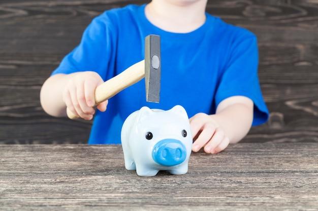 Копилка синей свиньи, которая готовится разбить молоток, чтобы получить монеты