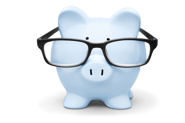 Blue piggy bank in glasses on background