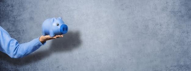コンクリートの壁の背景に、手に青い貯金箱。お金を節約するという概念、パノラマ画像。