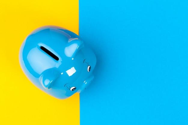 Blue piggy bank money box on bright colored