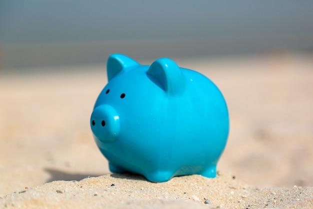 휴가에 따뜻한 좋은 바다 모래 저축에 파란색 돼지 저금통 돼지.